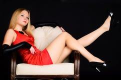Mujer joven en la alineada roja que se sienta en silla. Foto de archivo