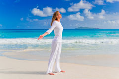 Mujer joven en la arena cerca del océano Foto de archivo