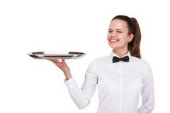 Mujer joven en la bandeja que se sostiene uniforme del camarero aislada sobre b blanco Fotografía de archivo