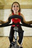 Mujer joven en la bici de ejercicio Foto de archivo libre de regalías