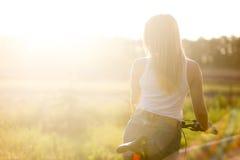 Mujer joven en la bici en campo Fotos de archivo libres de regalías