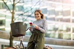 Mujer joven en la bici usando el teléfono móvil Fotografía de archivo libre de regalías