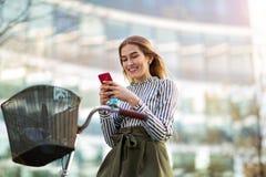 Mujer joven en la bici usando el teléfono móvil Fotos de archivo libres de regalías
