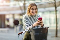 Mujer joven en la bici usando el teléfono móvil Fotografía de archivo