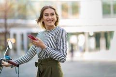 Mujer joven en la bici usando el teléfono móvil Imagenes de archivo