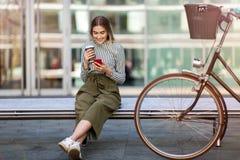 Mujer joven en la bici usando el teléfono móvil Foto de archivo libre de regalías