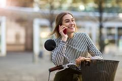 Mujer joven en la bici usando el teléfono móvil Foto de archivo