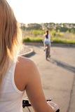 Mujer joven en la bicicleta en el camino Fotos de archivo libres de regalías