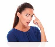 Mujer joven en la blusa azul que le mira Foto de archivo