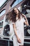 Mujer joven en la calle en el vestido blanco con el pelo del vuelo Fotografía de archivo