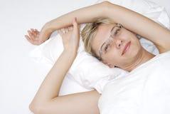 Mujer joven en la cama Imagenes de archivo