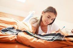 Mujer joven en la cama, dibujando en libro de colorear Fotografía de archivo libre de regalías