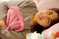 Mujer joven en la cama que siente el primer enfermo del problema de la menstruación del estómago fuerte Fotografía de archivo