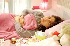 Mujer joven en la cama que siente el tiro medio del estómago del problema enfermo fuerte de la menstruación Imagen de archivo