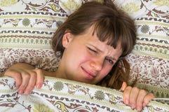 Mujer joven en la cama que tiene dolor de cabeza Imágenes de archivo libres de regalías