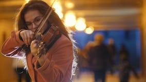 Mujer joven en la capa rosada que juega música del violín en subterráneo metrajes