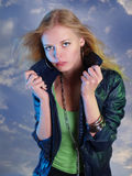 Mujer joven en la chaqueta de cuero en un fondo del cielo Fotos de archivo libres de regalías