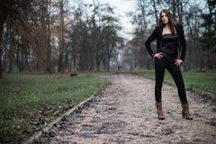 Mujer joven en la chaqueta negra que se coloca y que presenta en el bosque Fotografía de archivo