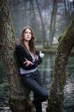 Mujer joven en la chaqueta que presenta en el árbol Imagenes de archivo