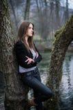 Mujer joven en la chaqueta que presenta en el árbol Imágenes de archivo libres de regalías