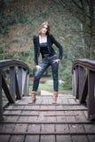 Mujer joven en la chaqueta que se coloca en el puente Foto de archivo libre de regalías