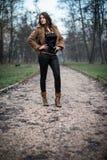 Mujer joven en la chaqueta que se coloca y que presenta en el bosque Fotografía de archivo