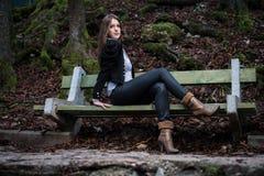 Mujer joven en la chaqueta que se sienta en el banco Foto de archivo libre de regalías