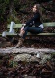 Mujer joven en la chaqueta que se sienta en el banco Fotografía de archivo