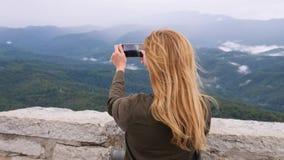 Mujer joven en la cima de la montaña que toma un selfie en la cámara lenta Mujer joven del caminante que toma a fotografías una v metrajes