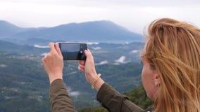 Mujer joven en la cima de la montaña que toma un selfie en la cámara lenta Mujer joven del caminante que toma a fotografías una v almacen de metraje de vídeo
