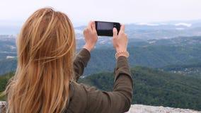 Mujer joven en la cima de la montaña que toma un selfie en la cámara lenta Mujer joven del caminante que toma a fotografías una v almacen de video