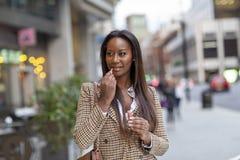 Mujer joven en la ciudad que pone en lipsgloss imagenes de archivo