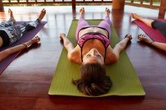 Mujer joven en la clase de la yoga que hace savasana Foto de archivo