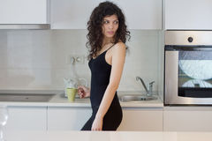 Mujer joven en la cocina imagen de archivo