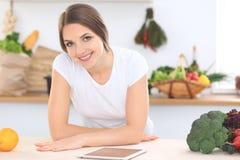Mujer joven en la cocina que hace compras en línea por la tableta y la tarjeta de crédito fotos de archivo