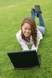 Mujer joven en la computadora portátil fotos de archivo