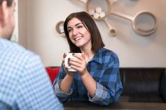 Mujer joven en la conversación en una tabla que lleva a cabo el A.C. Fotografía de archivo