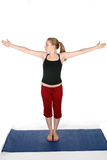 Mujer joven en la estera azul de la yoga con los brazos hacia fuera Fotos de archivo
