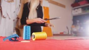 Mujer joven en la fábrica de costura que corta el paño con tijeras Hilo de coser en foco Tiro estático almacen de video