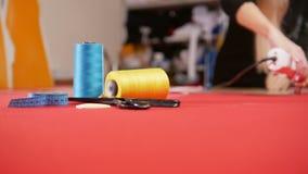 Mujer joven en la fábrica de costura que corta el paño Hilo de coser en foco Tiro estático almacen de video