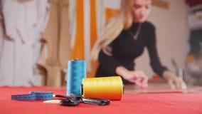 Mujer joven en la fábrica de costura que hace bosquejos en el paño Hilo de coser en foco Tiro estático metrajes