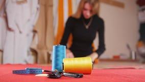 Mujer joven en la fábrica de costura que hace bosquejos en el paño rojo Hilo de coser en foco Tiro estático almacen de video