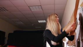Mujer joven en la fábrica de costura Una mujer pone una plantilla en la pared metrajes