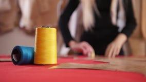 Mujer joven en la fábrica de costura Una mujer que hace bosquejos en el paño Hilo de coser en foco almacen de video