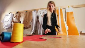 Mujer joven en la fábrica de costura Una mujer que toma la plantilla de la pared metrajes