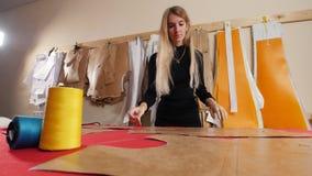 Mujer joven en la fábrica de costura Una mujer toma una plantilla de la pared almacen de video