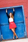 Mujer joven en la falda roja, puerta azul Fotos de archivo libres de regalías