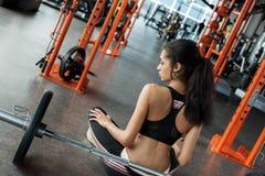 Mujer joven en la forma de vida deportiva del gimnasio que se sienta en actitud del loto cerca del barbell pensativo fotos de archivo libres de regalías