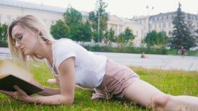 Mujer joven en la guita que miente en la hierba que lee un libro almacen de metraje de vídeo