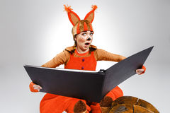 Mujer joven en la imagen de la ardilla roja con el libro grande Imagenes de archivo